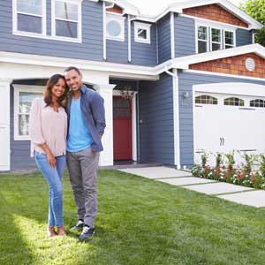 Couple standing in front of a new blue home