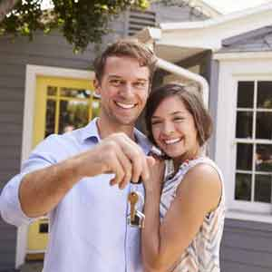 Young couple that are first time home buyers holding keys in front of their new house