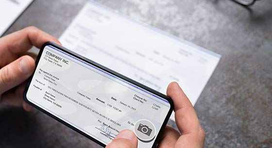 person using a phone to capture a photo of their check for mobile deposit