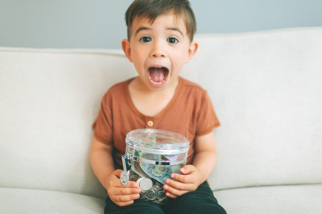 young boy excited about his jar of money