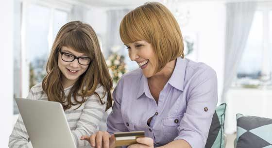 Mom and Daughter looking at computer, holding credit card
