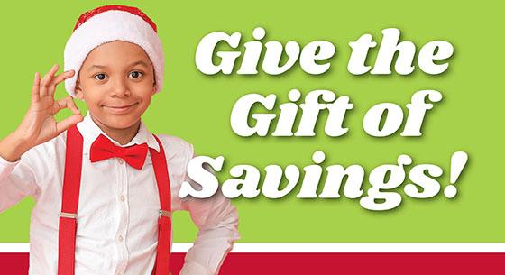Give the Gift of Savings! with a young boy in a santa hat on a green background